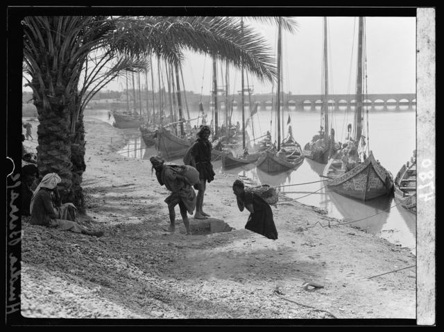 """Iraq. Hindiyah Barrage. About 48 miles S.E. of Baghdad. Row of """"Bellums,"""" river boats in foreground"""