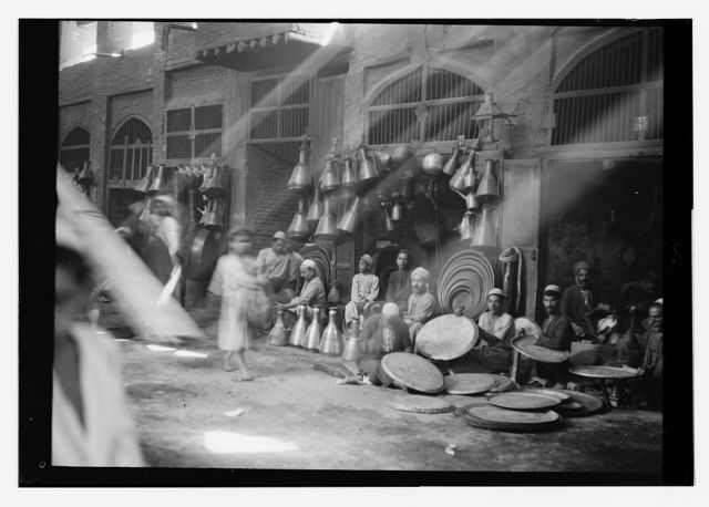 [Iraq. (Mesopotamia). Baghdad. Views, street scenes, and types. Typical copper store with jugs and trays]