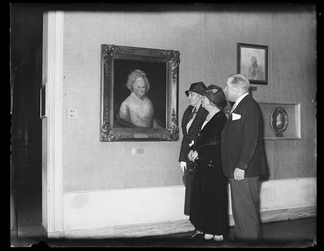 [Lou Hoover and group viewing portrait in gallery]