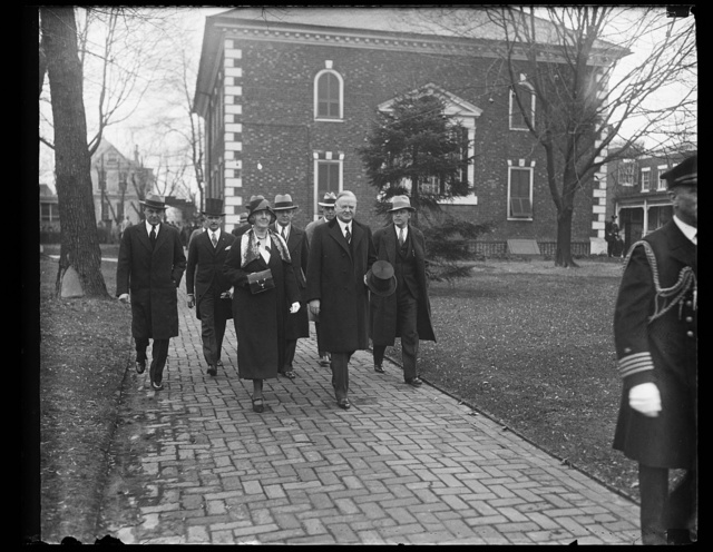 [Lou Hoover and Herbert Hoover strolling with group]