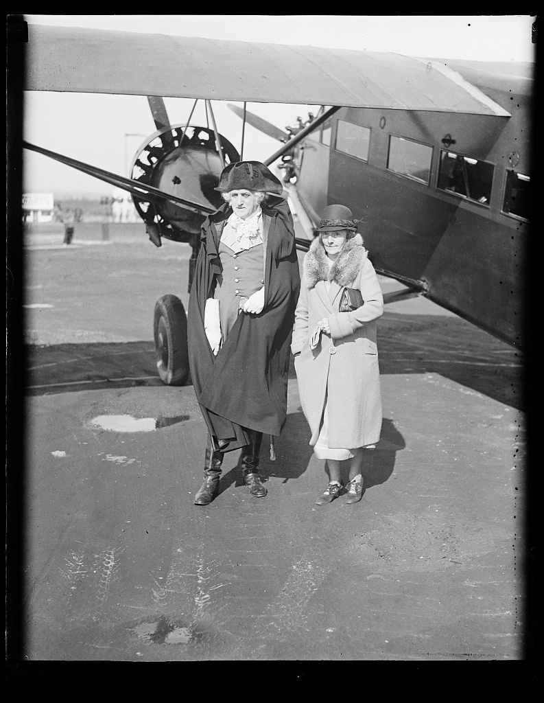 [Man dressed as George Washington and woman at airplane]