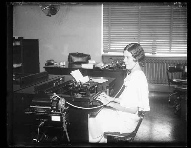 [Woman working at typewriter in office]