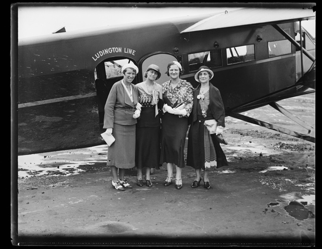 [Women standing next to Ludington Line airplane]