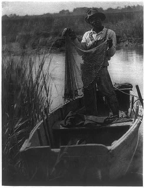 [African American man standing in boat holding fishing net]