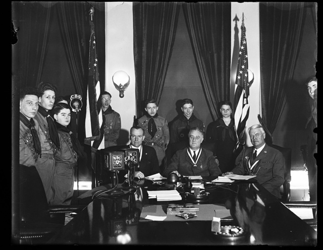APPEALS TO BOY SCOUTS. PRESIDENT ROOSEVELT APPEALS TO THE BOY SCOUTS OF AMERICA TO ASSIST IN CARRYING OUT THE ADMINISTRATION'S RELIEF CAMPAIGN. HE ADDRESSED THE BOYS OVER A NATION-WIDE RADIO HOOK UP. FROM THE LEFT: WALTER H. HEAD, NEW YORK, PRESIDENT OF THE BOY SCOUTS; PRESIDENT ROOSEVELT; AND JAMES E. WEST, CHIEF SCOUT EXECUTIVE