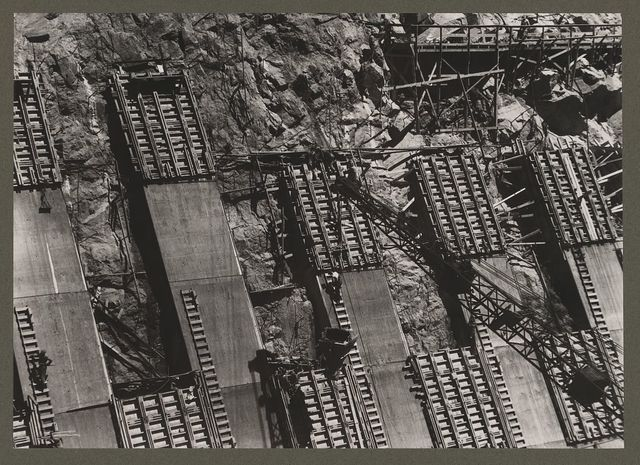 Boulder Dam, (i.e. Hoover Dam) between Arizona and Nevada. Placing concrete in the sidewall of the Nevada spillway. A 2 cubic yard bottom-dump bucket is being handled by crane. Note the manner in which the panels are staggered