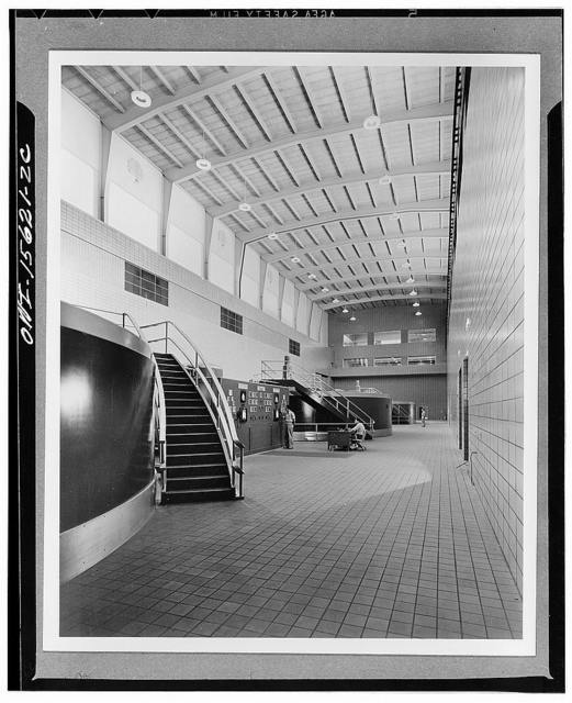 Chickamauga Dam and powerhouse. View of generator hall, looking towards reception room end. Upper row of three large windows is overlook for reception room. Three windows beneath are those of control room (compare with K 2313). Balcony for communication and view in front of control room windows. Roof is carried by rigid steel arches which spring from crane rail level; steel purlins, exposed precast concrete slab. Windows of hall are glass brick for insulation. Translucent plastic discs suspended from standard highboy lighting units conceal view or direct reflection of filaments and reflect spill light onto ceiling, thus generally brightening the space. Floor is ceramic tile; walls, glazed structural tile up to crame rail, exposed concrete above