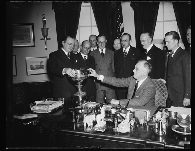 CHIEF EXECUTIVE PRESENTS PRESIDENT'S CUP TO WINNER OF REGATTA. WASHINGTON, D.C. PRESIDENT ROOSEVELT TODAY PERSONALLY PRESENTED THE PRESIDENT'S CUP TO HERBERT A. MENDELSON OF DETROIT, WINNER OF THE PRESIDENT'S CUP REGATTA ON THE POTOMAC RIVER LAST SEPTEMBER. L TO R: HERBERT A. MENDELSON; GORDON LEECH, CHAIRMAN OF THE PRESIDENT'S CUP REGATTA ASSOCIATION; JAMES A. COU[...]OR, GENERAL CHAIRMAN OF THE 1937 REGATTA; HARRY P. SOMMERVILLE, EXECUTIVE SECRETARY
