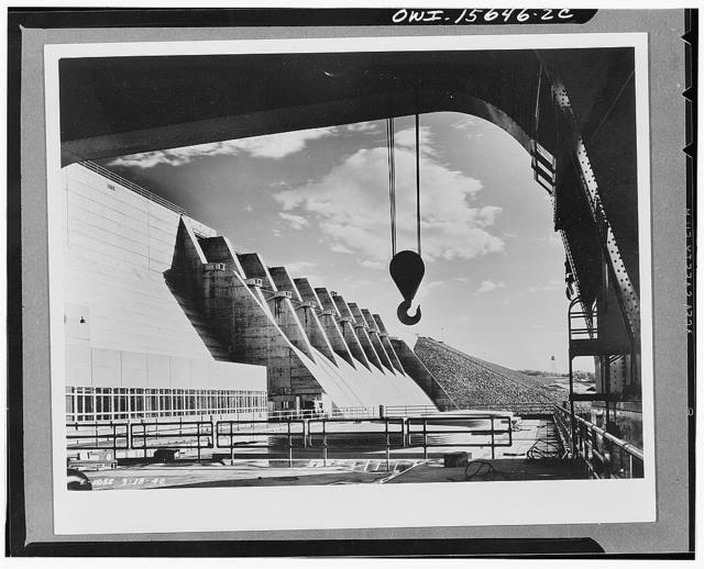 Dams under construction. Cherokee Dam is the latest headwaters dam to be completed. It is a semioutdoors type structure, the covers over the three initial generating units show in the picture behind the railing in front. The office wing of the control building is on the left. The shot is taken between the legs of the gantry crane which is used for installation and removal for repairs of turbines and generators. The cage-like steel contraptions mounted on the spillway piers are the anchorages for the floodgate hinges