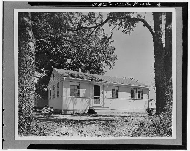 Demountable employee housing. Three-bedroom war workers' house constructed in five slices. On this project, where the houses went into an existing community in Alabama to provide housing for employees of chemical and metallurgical industries of the TVA (Tennessee Valley Authority), the local desire for traditional appearance was accommodated by the use of a pitched roof. Each side of the roof is hinged at the eaves and is laid down, during transport, over the ceiling to bring overall height within normal highway clearances