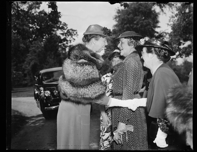 ER [i.e., Eleanor Roosevelt] shaking hands with woman in a row. Warm weather