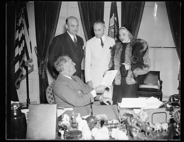 FDR [Franklin Delano Roosevelt] at desk receiving plaque from woman. 2 men