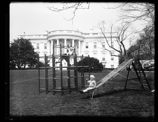 FIRST PHOTOGRAPH OF ROOSEVELT GRANDCHILDREN AT PLAY ON WHITE HOUSE GROUNDS. FOR THE FIRST TIME SINCE THE LAST ROOSEVELT ADMINISTRATION THE SOUTH LAWN OF THE WHITE HOUSE HAS BEEN TURNED INTO A CHILDREN'S PLAYGROUND. LITTLE SISTIE AND 'BUZZIE' DALL, GRANDCHILDREN OF PRESIDENT AND MRS. FRANKLIN D. ROOSEVELT, ARE SHOWN AT PLAY THIS MORNING. THEY ARE THE CHILDREN OF MR. AND MRS. CURTIS DALL