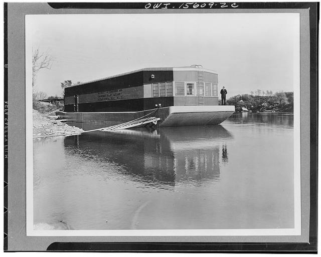General planning. Refrigerated barge designed and built by the TVA (Tennessee Valley Authority) in collaboration with the University of Tennessee to encourage the fruit and vegetable freezing industry in the Valley and the marketing of its products over the inland waterways system. The architects of the Authority cooperated in the design of the superstructure which was erected on a standard steel barge. Sheathing is of T and G boards, roof of galvanized sheet metal. Glass-enclosed cabin at one end houses refrigerating machinery, at other end crew's quarters. Colors are light shades of grey, with upper and lower bands of superstructure in maroon. Visible part of windows is the screen frame; glazed sash is behind and its frame is painted black to eliminate its competetion with the screen frame and its...