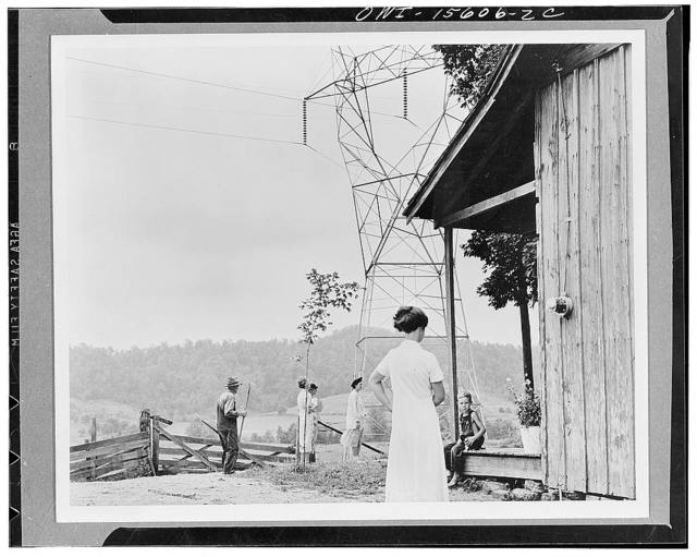 General planning. This photograph is included in the series as a vivid document on the impingement of Twentieth Century technology upon the neglected and backward rural scene. The meter on the wall of the rural shack indicates that it now receives its share of electricity from the power carried overland by the huge TVA (Tennessee Valley Authority) transmission line. TVA program must resolve the conflict between between modern and ancient ways of life so that individuals, similar to those which are shown in the picture, will be benefited