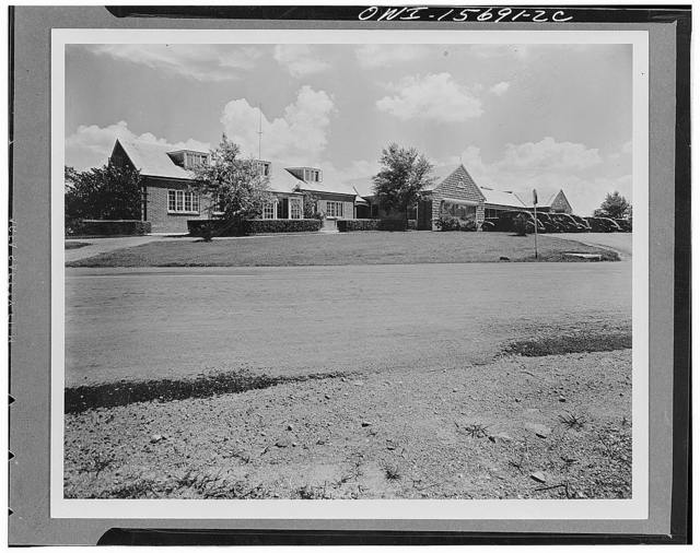 Group of administrative and store buildings in the town of Norris. The left wing houses the town management offices. The middle portion includes a drugstore, food store, general store, and beauty parlor; the far wing, of which only part is visible, houses the post office and telephone exchange. In addition to serving the needs of the town of Norris, this group was conceived as a demonstration of acceptable design for facilities which normally tend to be ugly, disorganized, and neglected in the average small town