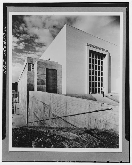 Guntersville Dam and powerhouse. End view of powerhouse toward land approach. Enormous glazed door toward generator hall opens in sections to permit passage of heavy equipment for installation or repair. Large glass brick panel illuminates stairway which leads to electrical rooms below and office suite above. Similar stair access at other end of powerhouse