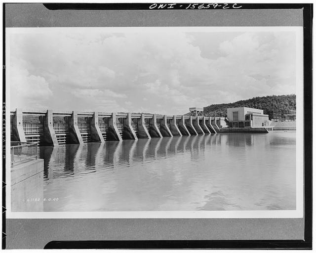 Guntersville Dam and powerhouse. General view of spillway and powerhouse. The latter encloses three units, is intended to extend eventually to a fourth. Note one of two traveling gantry cranes on spillway deck. Main generator hall built in brick because it is in flood-proof portion; downstream bay which houses control equipment in lower stories and offices above is in concrete on account of flood hazard