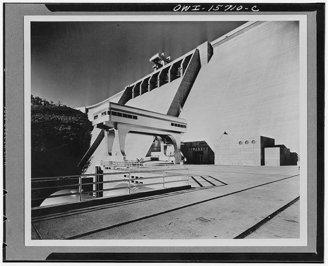 Hiwassee Dam and powerhouse. Detailed view of dam with powerhouse in foreground, one unit installed at the time photograph was taken. Powerhouse is semi-outdoor type in that crane for installing and removing generator is exposed. Deck visible in picture is roof of power plant proper with control building projecting above