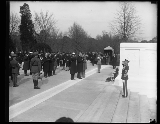 HONORS UNKNOWN DEAD. PRESIDENT ROOSEVELT, IN HIS FIRST ARMISTICE DAY OBSERVANCE IN THE WHITE HOUSE, PLACES A WREATH UPON THE TOMB OF THE UNKNOWN SOLDIER IN ARLINGTON CEMETERY. THE CHIEF EXECUTIVE STANDS BETWEEN TWO WHITE HOUSE AIDES AS TAPS ARE SOUNDED. THE TWO MEN IN CIVILIAN CLOTHES DIRECTLY BEHIND THE PRESIDENT ARE SECRETARY OF WAR DERN, LEFT, AND SECRETARY OF NAVY SWANSON