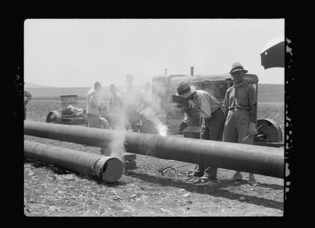 Laying of the Iraq Petroleum Company's pipe line across the Plain of Esdraelon, July 1933. Welding the pipe line. By electric fleet weld method