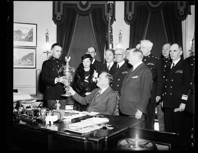 MARINES AVIATION AWARD GIVEN. PRESIDENT ROOSEVELT PRESENTS FIRST LIEUTENANT DAVID LORD, COMMANDING OBSERVATION SQUADRON SEVEN OF THE MARINE CORPS, WITH THE HERBERT SCHIFF TROPHY, GIVEN ANNUALLY TO THE SQUADRON OR UNIT WHICH LOGS THE GREATEST NUMBER OF FLIGHT HOURS WITH THE MINIMUM OF ACCIDENTS. STANDING ON THE RIGHT IS COL. H.L. ROOSEVELT, ASSISTANT SECRETARY OF THE NAVY
