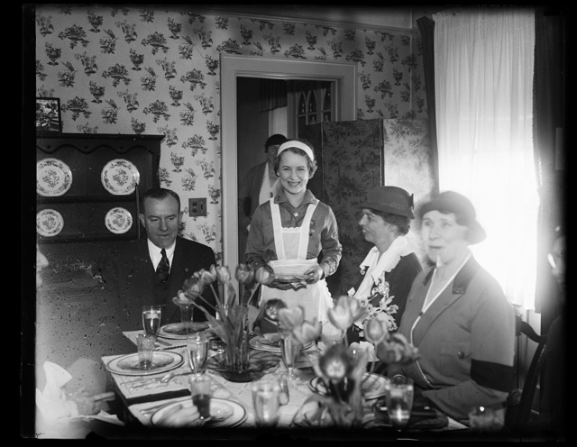 MRS. ROOSEVELT IS GUEST OF GIRL SCOUTS AT 15-CENT LUNCHEON. MRS. FRANKLIN D. ROOSEVELT ENJOYED A 15-CENT LUNCHEON TODAY AS GUEST OF THE GIRL SCOUTS IN THEIR 'LITTLE HOUSE' IN WASHINGTON. ON THE LEFT IS WALTER W. HEAD, PRESIDENT OF THE BOY SCOUTS OF AMERICA. FLORENCE YEAGER IS THE GIRL SCOUT SERVING THE FIRST LADY OF THE LAND