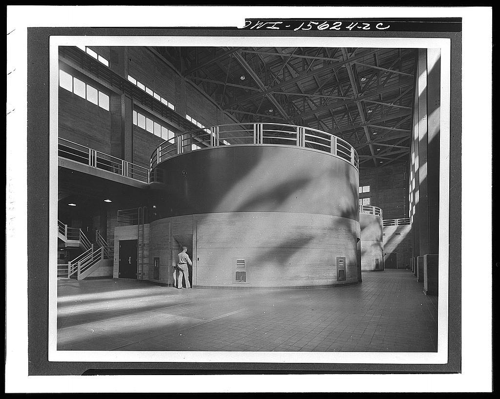 Norris Dam and powerhouse. Norris generator hall. Turbines are enclosed in and below round concrete housings, generators are contained in steel upper portion. In peacetime visitors are admitted to balcony shown at left to inspect control room and are then taken to generator floor. Roof trusses are considered unattractive; later projects are framed with rigid steel arches