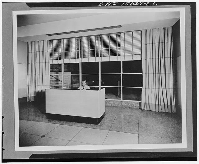 Norris Dam and powerhouse. View of reception room at the TVA's (Tennessee Valley Authority) first project which was experimental and somewhat small compared to visitors' traffic in peacetime. Guard sits behind special desk with raised rim, used by visitors when they register. Large window behind guard looks out over switchyard and over route taken by visitors upon completion of their inspection trip