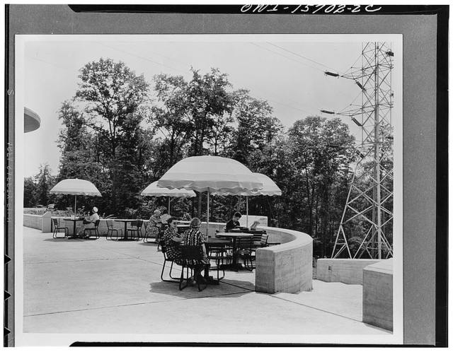Overlook terrace in front of Norris visitors' building described under K 1868 and K 1867. Refreshments served under gay umbrellas added a new note to the resources of pleasant living in this area which was notably deficient in facilities for outdoors enjoyment. The place proved a major attraction and has thousands of visitors on holidays. The broad stairs which begin at either side of the semicircular terrace lead to a pathway connecting to the picnic grounds
