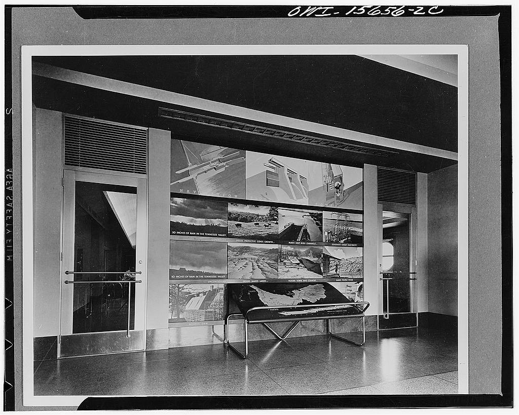 Pickwick Dam. Reception room of a powerhouse which is somewhat difficult to reach (therefore, supplementary visitors' facilities were developed at the opposite end of the dam in separate buildings). Rest rooms, elevators, stairway, overlook balcony, and control room can be viewed either through glass doors from this room or from large plate glass openings of the overlook balcony. Terrazzo floor and base, burlap covered plaster walls, acoustic plaster ceiling. Graphic display is in a shallow wall niche between control room doors; top line shows three functions of projects in cross-sectional perspectives; photographs elaborate on TVA (Tennessee Valley Authority) program; map of valley is  applied to specially constructed movable table