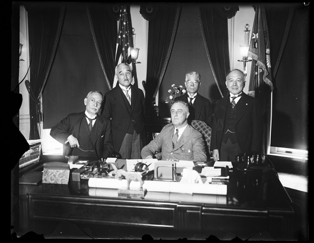 PRESIDENT ROOSEVELT AND JAPANESE DELEGATION IN CONFERENCE AT WHITE HOUSE. TO EXCHANGE VIEWS ON ECONOMIC CONDITIONS AND STUDY THE FOREIGN EXCHANGE SITUATION, PRESIDENT ROOSEVELT TODAY CONFERRED WITH VISCOUNT ISHII AND MEMBERS OF HIS DELEGATION AT THE WHITE HOUSE. IN THE PHOTOGRAPH, L TO R: VISCOUNT ISHII; PRESIDENT ROOSEVELT; MRS. EIGO FUKAI, VICE GOVERNOR OF THE BANK OF JAPAN; AND AMBASSADOR KATSUJI DEBUCHI
