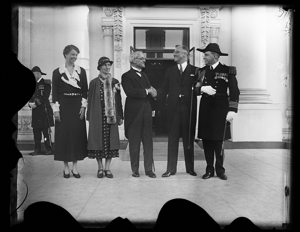 PRESIDENT ROOSEVELT GREETS PRIME MINISTER MacDONALD AT WHITE HOUSE. PRIME MINISTER RAMSAY MacDONALD, OF GREAT BRITAIN, AND HIS DAUGHTER ISHBEL WERE GIVEN A WARM WELCOME BY PRESIDENT AND MRS. ROOSEVELT WHEN THEY ARRIVED AT THE WHITE HOUSE TODAY. WHILE IN WASHINGTON THE BRITISH STATESMAN WILL STUDY THE SHIFTING SCENE OF WORLD ECONOMICS WITH PRESIDENT ROOSEVELT. IN THE PHOTOGRAPH, L TO R: MRS. ROOSEVELT; MISS ISHBEL MacDONALD; PRIME MINISTER MacDONALD; PRESIDENT ROOSEVELT; AND CAPT. WALTER VERNOU, WHITE HOUSE NAVAL AIDE