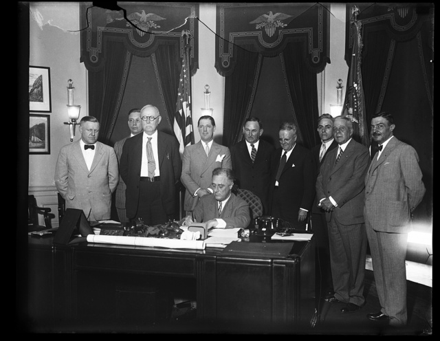 PRESIDENT SIGNS SMALL HOME LOAN MEASURE. PRESIDENT ROOSEVELT TODAY SIGNED THE BILL PROVIDING FOR A $2,000,000,000 REFINANCING OF SMALL HOME MORTGAGES TO PUT THEM ON LOWER INTEREST RATE. THE ADMINISTRATION HOPES TO HAVE THE LAW IN ACTIVE OPERATION WITHIN A MONTH. IN THE PHOTOGRAPH CAN BE SEEN: WILLIAM F. STEVENSON, CHAIRMAN OF HOME LOAN BANK BOARD; T. DWIGHT, MEMBER OF BOARD; RUSSELL HAWKINS, MEMBER; A. E. HUTCHISON, SECRETARY OF BOARD; HO..RUSSELL, GENERAL COUNSEL OF BOARD; CARRO[...], MEMBER; WALTER H. NEWTON, MEMBER; REP. WILLIAM F. BRUNNER, NY; SEN. JOSEPH T. ROBINSON, AR.