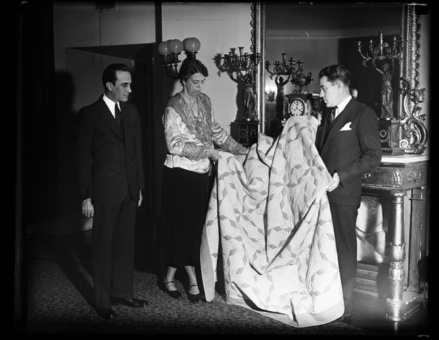 PRIZE QUILT GIVEN MRS. ROOSEVELT. THE QUILT WHICH WON PRIZES AT THE WORLD FAIR IN CHICAGO IS PRESENTED TO MRS. ROOSEVELT BY E.J. CONDON. L.T. CONWAY VIEWS THE CEREMONY. BOTH MEN ARE CONNECTED WITH A MERCHANDISING CONCERN DOING BUSINESS ON A NATIONWIIDE SCALE. THE PRIZE WINNING QUILT WAS MADE BY MARGARET ROGERS CADEN OF LEXINGTON, KY