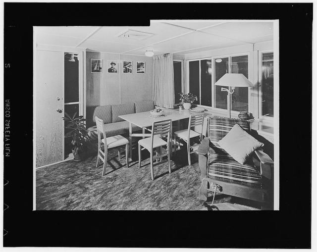This is a partial view of the living room showing the dinette corner with its collapsible table and chairs. The other end of the living room, not shown here, contains a studio couch which sleeps two. In addition, the trailer house contains a fully equipped kitchenette, a bedroom with built-in double bed and a large amount of storage space, and a bathroom. Walls are of plywood in natural finish, ceiling is plywood painted white, floor is plywood covered with inlaid linoleum. The square panel in the center of the ceiling is a ventilator which can be cranked open in summer. All windows are of the sliding type to occupy minimum space and to minimize the use of critical hardware