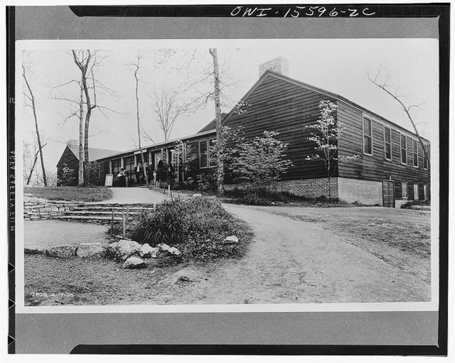 This structure is fairly typical of the kind of accomodations provided for the recreation of unmarried TVA (Tennessee Valley Authority) construction employees of both sexes. Whenever possible such structures are later converted to fill permanent needs of the region. During the construction of Norris Dam, the structure included a large lounge, a refreshment and lunch space, and auditorium with stage and projection room, capable of accomodating 300, library and reading room, barber and beauty shop, restrooms, administrative office and committee or lecture rooms. The auditorium was converted into a gymnasium. It now serves as a community building for the permanent residents of the town of Norris, a regular restaurant having replaced the refreshment room, while the county art center has been installed in place of the library, and the offices, display room, and storage room of the handicraft cooperative have taken up the space formerly occupied by the barber and beauty shop