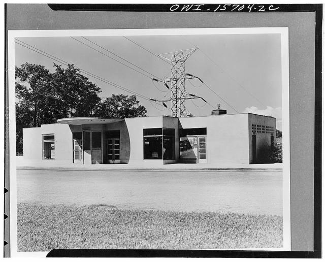 Visitors' building on the east abutment of Norris Dam constructed of cinder concrete blocks with stucco finish. Guard booth under center canopy controls central hall of structure and project parking space in front; also has view of terrace on opposite side. Wings house refreshment counter, a store of the cooperative merchandising organization for local handicraft products and in the windowless extremities of the wing, visitors' toilets