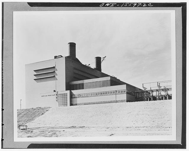 Watts Bar steam plant. General view of the plant still under construction. When finished, four turbines will generate 240,000 kva. Tall portion houses boilers, bunkers, and conveyor in a simple brick cube, ninety-odd feet tall, above ground and several stories below. Lower portion at right is turbine hall with glass brick upper part and corrugated transite spandrel above. Wing in front houses machine shop on first floor, offices on second. Main entrance is marked by large glazed opening with flagpole next to it, windowless portion to left of ot contains employee lockers and toilets