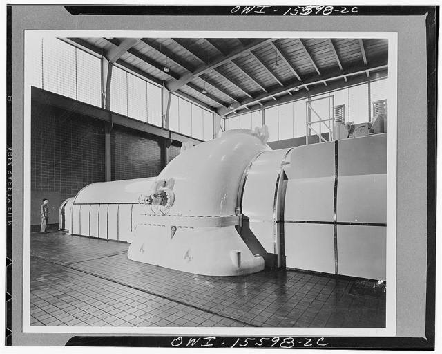 Watts Bar steam plant. Partial view of generator hall with one of 60,000 kva turbines in foreground. Gray ceramic tile floor, blue-gray tile walls, exposed steel work designed for maximum simplicity with rigid frame roof arches, precast concrete slabs, continuous glass brick above crane rail level. Units in light cream with a rich tan over portions of the machinery subject to particularly high temperatures. Light color over other portions compels first-class maintenance, also emphasizes importance of units by concentrating attention