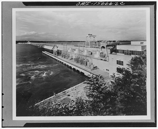 Wheeler Dam and powerhouse. General view showing four generators of the semi-outdoor type installed. Space is left for addition of four more. Navigation lock in distance, bulkhead section, spillway and power plant following left to right. Terrace in front of top story of control buildings for visitors' inspection of the project