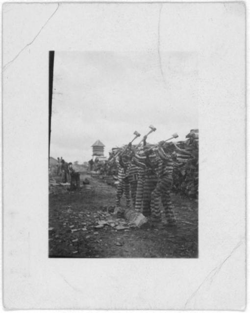 [African American convicts working with axes, watchtower in background, Reed Camp, South Carolina]