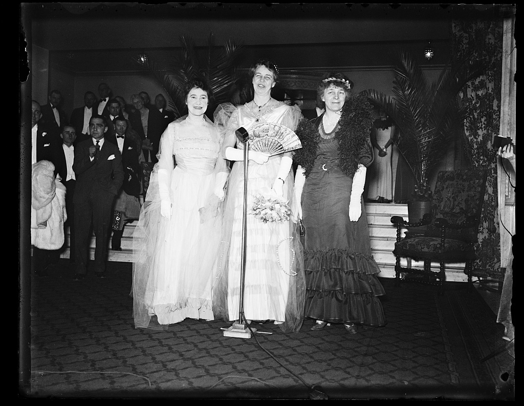 AS THEY DRESSSED IN THE 1900'S. THESE THREE WOMEN, MRS. MARY HARRIMAN RUMSEY, NEW YORK MILLIONAIRE, LEFT, MRS. FRANKLIN D. ROOSEVELT, AND MRS. ISABELLA GREENWAY, REPRESENTATIVE FROM ARIZONA, ATTENDED THE JUNIOR LEAGUE BALL AT THE MAYFLOWER HOTEL IN WASHINGTON FRIDAY NIGHT IN THE GOWN THEY WORE THE NIGHT THEY MADE THEIR DEBUTS. MRS. RUMSEY, WHO IS CHAIRMAN OF THE CONSUMERS ADVISORY BOARD OF THE N.R.A., ORGANIZED THE FIRST JUNIOR LEAGUE UNIT IN THE COUNTRY IN NEW YORK CITY. THESE THREE WOMEN HAVE BEEN PERSONAL FRIENDS FOR MANY YEARS