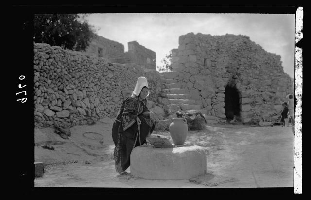 Bethlehemite woman at the country cistern, watchtower in background