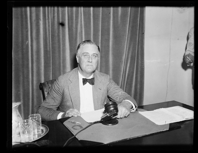 CHIEF ASKS PEOPLE TO JUDGE RECOVERY PROGRAM. PRESIDENT ROOSEVELT, AS HE PREPARED TO ADDRESS THE NATION OVER THE RADIO, CALLS UPON THE PEOPLE TO JUDGE THE MERIT OF THE RECOVERY PROGRAM. THE RADIO ADDRESS WAS MADE JUST BEFORE THE PRESIDENT LEFT ON HIS SUMMER VACATION. NOTICE THE BLACK BOW WORN BY THE CHIEF EXECUTIVE