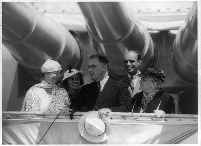 [Eleanor Roosevelt, Mrs. James (Betsy Cushing) Roosevelt, Franklin D. Roosevelt, James Roosevelt, and Franklin Roosevelt's mother, Mrs. James (Sara) Roosevelt, posed standing under big guns on battleship Indianapolis, May 31, 1934]
