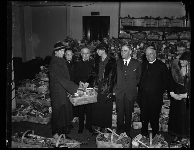 FIRST LADY HELPS SALVATION ARMY DISTRIBUTE BASKETS TO POOR. MRS. FRANKLIN D. ROOSEVELT, IN A DAY OF CHARITABLE ACTIVITIES, JOINED WITH THE SALVATION ARMY IN DISTRIUTING BASKETS OF FOOD TO THE NEEDY. SHE IS SHOWN HERE PRESENTING A BASKET TO MRS. MAY JOHNSON. FROM THE LEFT: MRS. JOHNSON; MRS. JAMES ASHER; MAJOR JAMES ASHER, HEAD OF THE SALVATION ARMY IN WASHINGTON; MRS. ROOSEVELT; SECRETARY OF WAR DERN; AND THE RT. REV. JAMES FREEMAN, BISHOP OF WASHINGTON