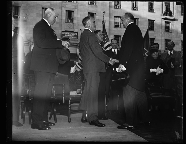 INFORMALITY PLUS. THIS PHOTOGRAPH SHOWS PMG FARLEY, LEFT AND PRESIDENT ROOSEVELT GREETING HIS ATTORNEY GENERAL CUMMINGS AT THE DEDICATION OF THE DEPARTMENT OF JUSTICE BUILDING