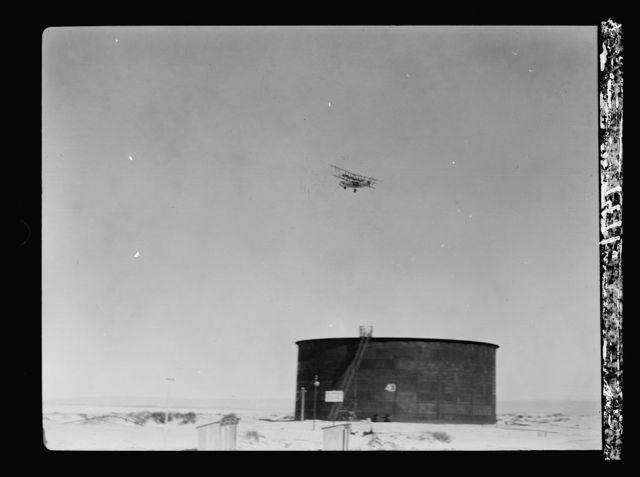 I.P.C. [i.e., Iraq Petroleum Company]. Tank in Haifa terminus with plane in sky