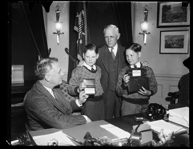 NATION'S CHIEF EXECUTIVE RECEIVES GOLD BASEBALL PASS FROM PRESIDENT OF WASHINGTON CLUB. PRESIDENT ROOSEVELT WAS PRESENTED WITH A GOLD SEASON BASEBALL PASS TODAY BY PRESIDENT CLARK C. GRIFFITH OF THE WASHINGTON BASEBALL CLUB. AT THE SAME TIME MRS. ROOSEVELT WAS GIVEN A GOLD PASS SET IN A LEATHER POCKETBOOK. WITH GRIFFITH ARE HIS TWO ADOPTED SONS JIMMY AND BILLY